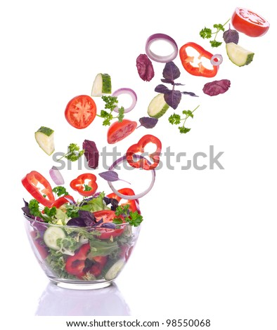 Vegetables for a salad of lettuce falling. Isolated on white.