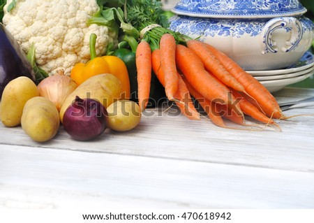 vegetables for soup on a white table with bowl and tablespoon