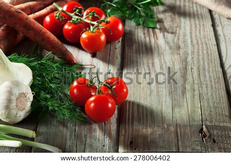 vegetables from the garden, carrots, cherry tomatoes, onions, parsley, dill and young garlic on a wooden table