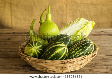 Vegetables in  a basket on wooden table, vintage still life - stock photo