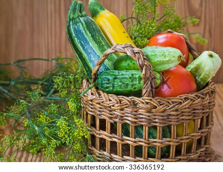 Vegetables in a wicker basket on a wooden background - stock photo