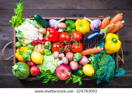 Vegetables in wooden box on dark background. - stock photo