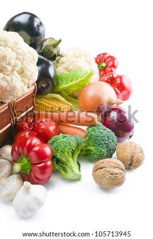 Vegetables. Mix of fresh ripe vegetables placed in a wicker basket and around isolated on white background.