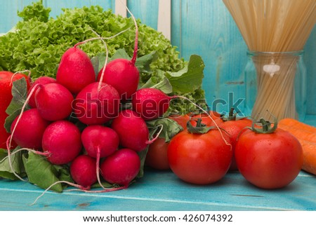 vegetables mix : some raw ripe fresh tomatoes, carrots, garlic,radishes, carrots, peppers, lettuce and cabbage over blue table - stock photo