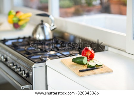 Vegetables on chopping board on counter top in kitchen - stock photo