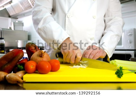 Vegetables on cutting board and chef hands detail, restaurant kitchen on background - stock photo