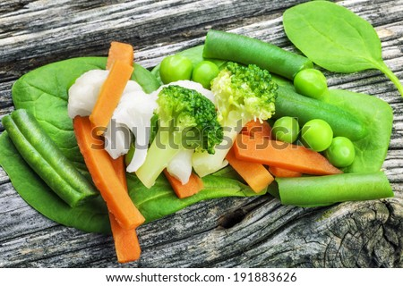 Vegetables on old wooden table with lettuce leaves
