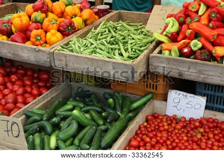 Vegetables on sale at a greek market stall - okra, cucumber,cherry tomatoes, plum tomatoes, capsicums and peppers, - stock photo