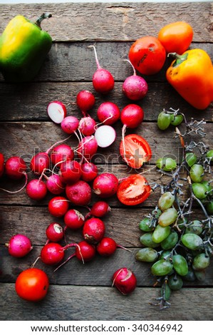 Vegetables on vintage wood background - autumn harvest. Fresh vegetable on wooden table. Top view. Autumn harvest: grapes, radishes, tomatoes, peppers . Autumn background. Ripe vegetables. - stock photo