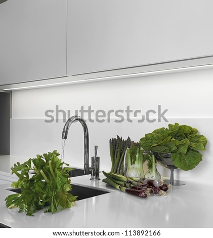 vegetables on white worktop in the modern kitchen near to sink - stock photo