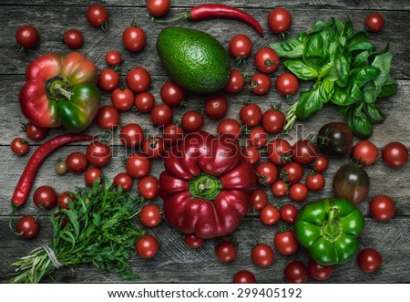 vegetables on wooden table in rustic style. Tomatoes, pepper, avocado, basil - stock photo