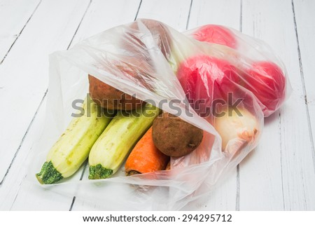 Vegetables packed in a plastic bag on a white wooden table