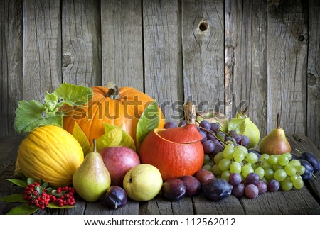 Vegetables pumpkins and fruits in autumn halloween season still life on vintage wooden boards - stock photo