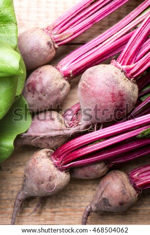 Vegetables, salads, beetroot, spinach. On a wooden background.