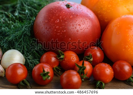 Vegetables (tomatoes, garlic, parsley, dill) on wooden table