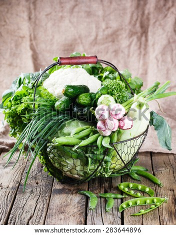 Vegetables variety in a wire basket on a wooden background. selective focus - stock photo