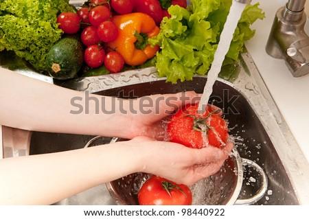 Vegetables washing, splashing water, fresh salad preparation - stock photo