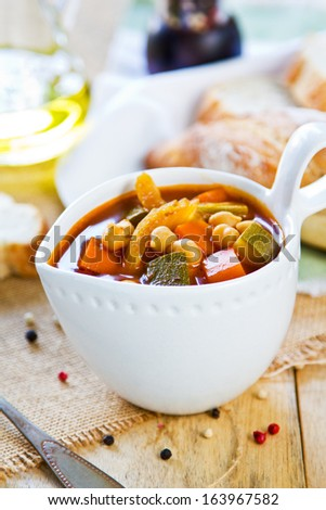 Vegetables with Chickpea soup by loaf of bread - stock photo