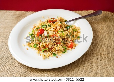 Vegetarian and healthy risotto from buckwheat and couscous with roasted tomato and coriander leaf on white plate on rustic coarse cloth background - stock photo