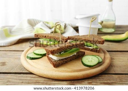 Vegetarian avocado sandwich with dark rye bread on a wooden board - stock photo