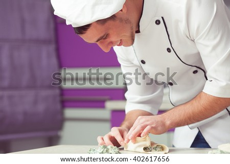 Vegetarian bakery concept. Smiling chef cook in uniform putting filler of spinach and soft feta cheese on slice of puff pastry and making french chausson. Close up. Indoor shot - stock photo