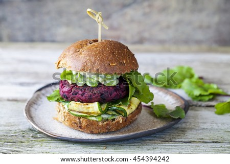 Vegetarian beetroot burger with grilled courgettes and mashed broad beans