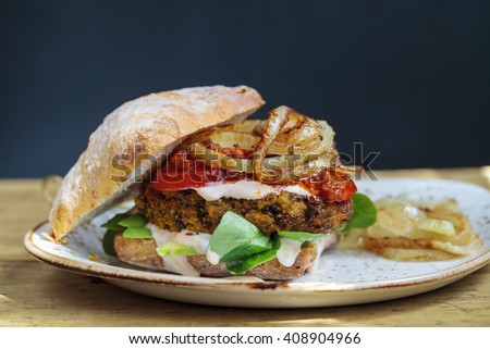 Vegetarian burger made from butternut squash and lentils with fried onion, greens and sun dried tomato paste