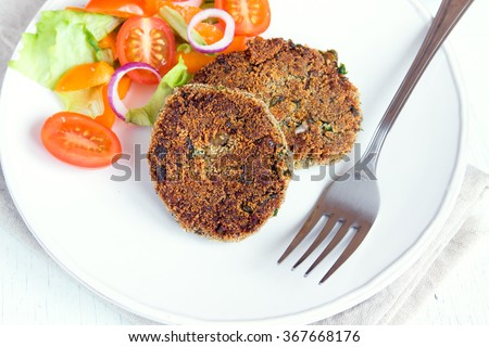 Vegetarian burger patties with vegetable salad on white plate - stock photo