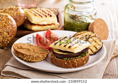Vegetarian burger with grilled cheese, eggplant and pesto - stock photo