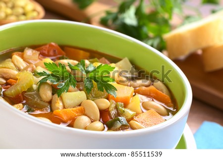 Vegetarian canary bean soup made of canary beans, celery, carrot, potato, tomato, leek, green onions garnished with parsley (Selective Focus, Focus one third into the soup and the front of parsley) - stock photo