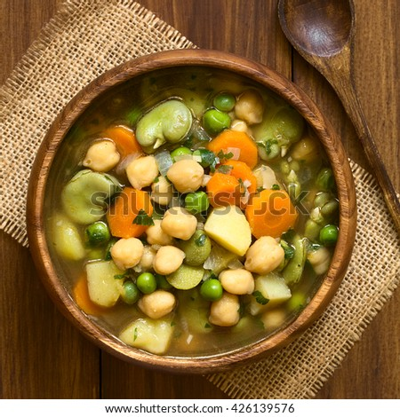 Vegetarian chickpea soup with carrot, broad bean (fava bean), pea, potato, onion, garlic and parsley served in wooden bowl, photographed overhead on wood with natural light