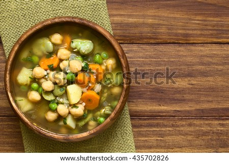 Vegetarian chickpea soup with carrot, broad bean (fava bean), pea, potato, onion, garlic and parsley served in wooden bowl, photographed overhead on wood with natural light - stock photo