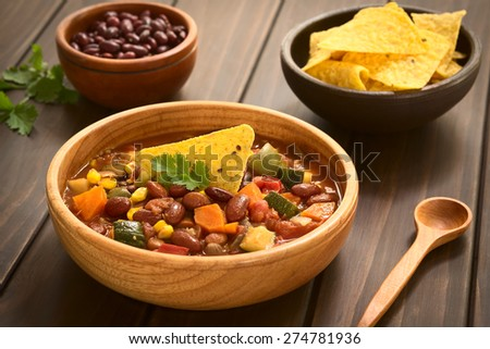 Vegetarian chili dish with kidney bean, carrot, zucchini, bell pepper, sweet corn, tomato, onion, garlic in wooden bowl, photographed with natural light (Selective Focus, Focus on the garnish)    - stock photo