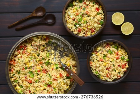 Vegetarian couscous salad made with bell pepper, tomato, cucumber, red onion and sweet corn kernels, wooden spoons and lemon on the side. Photographed overhead on dark wood with natural light.