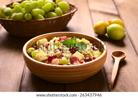 Vegetarian couscous salad with grapes, pomegranate, walnuts, cheese, lime and mint in wooden bowl photographed with natural light (Selective Focus, Focus on the mint leaf on the dish)  - stock photo