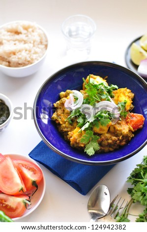 Vegetarian curry, panir and peas garnished with coriander and onion, in a blue bowl on a white background