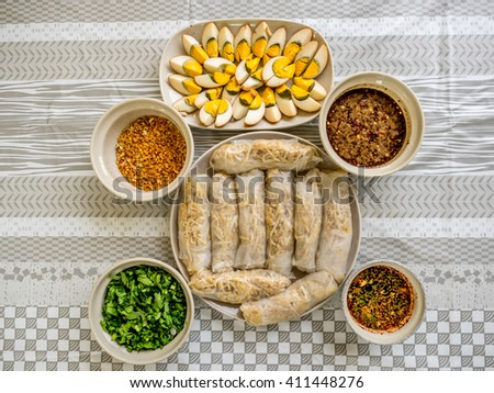 Vegetarian egg rolls, chopped tofu mixed with bean sprouts, served with eggs and assorted dressing comprising of fried garlic, chopped Chinese Parsley and chopped green onions, and soy sources  - stock photo