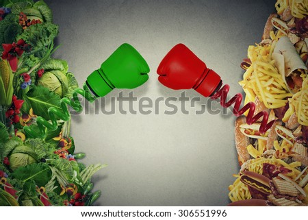 Vegetarian food fighting unhealthy junk food with boxing gloves punching each other. Diet battle nutrition concept. - stock photo