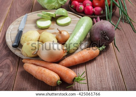 Vegetarian food. Vegetables prepared for a meal on a wooden table. Round wooden board for cutting