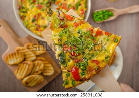 Vegetarian frittata with spinach, prosciutto and microgreens, baked baguette, served with woman hands - stock photo