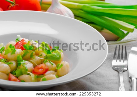 Vegetarian gnocchi with spring onions and tomatoes, herbs, olive oil and garlic