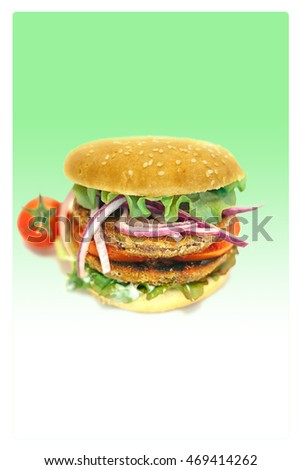 vegetarian hamburger with lettuce, tomato, onion and bun in green background