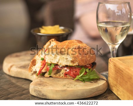 Vegetarian Italian Style Red Pepper Ciabatta Bread Sandwich with a Glass of White Wine On a Wooden Serving Board - stock photo