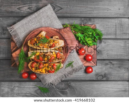 Vegetarian lunch Baked stuffed white eggplant stuffed with Baked and fresh vegetables, pumpkin, cherry tomatoes, chopped eggplant pulp, dill on gray background wooden surface, board, burlap, top view - stock photo