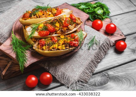 Vegetarian lunch Baked stuffed white eggplant stuffed with Baked and fresh vegetables, pumpkin, cherry tomatoes, chopped eggplant pulp, dill, parsley on gray background wooden surface, board, burlap - stock photo