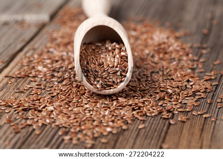 Vegetarian organic nutrition flax seeds with omega fat in spoon on vintage wooden background - stock photo
