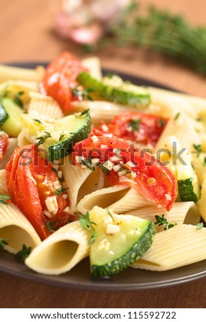 Vegetarian penne pasta dish with baked zucchini and tomato spiced with thyme and garlic (Selective Focus, Focus one third into the pasta dish) - stock photo
