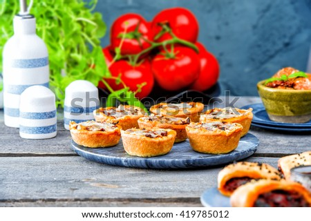 vegetarian pies with eggplant, red peppers, mushrooms with cheese. Picnic table with salty muffins, quiche, labneh,fresh tomatoes, mint on the old gray wooden table on stone texture background - stock photo