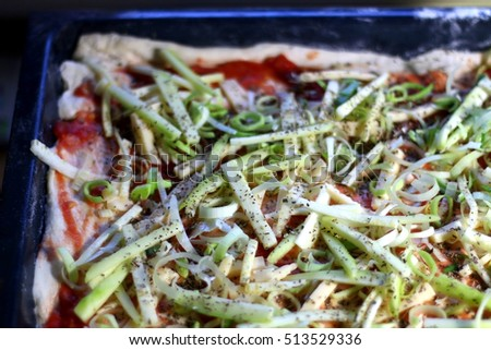 Vegetarian pizza in a pan, with tomato sauce, cheese, zucchini, leek and oregano, before baking. Selective focus.