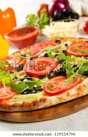 Vegetarian pizza on a wooden board - stock photo